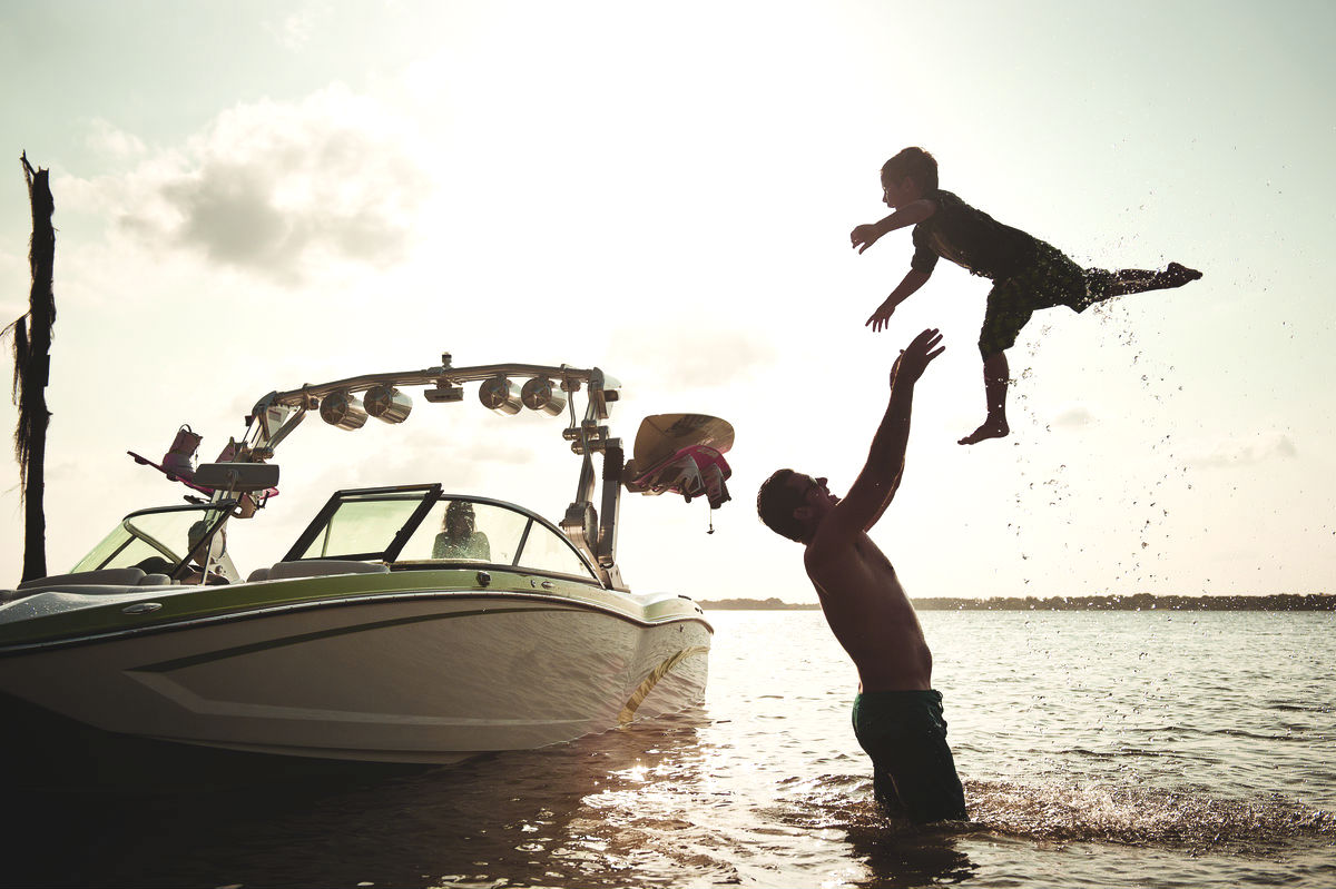 adult throwing child in the air next to ski boat